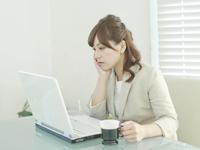 頬杖を突きながらパソコンで作業している女性