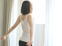 目覚めたばかりの女性が窓際で朝の光を浴びながら伸びをしている